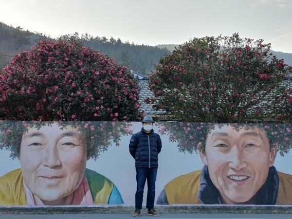 신안 암태도의 벽화 앞에서 국제웰빙전문가협회장 김용진 교수(사진자료)